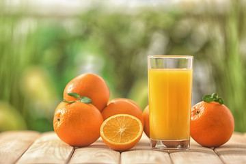 Glass of fresh orange juice on wooden table outdoors