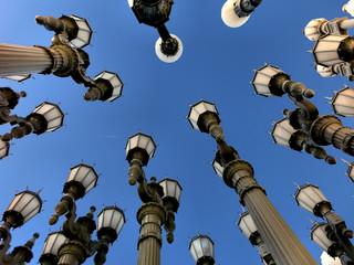 Streetlight lamps against blue sky