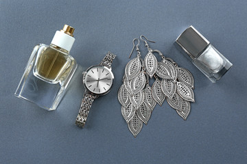 Bottle of perfume, accessories and nail polish on grey background