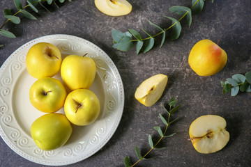Plate with ripe yellow apples on grey background