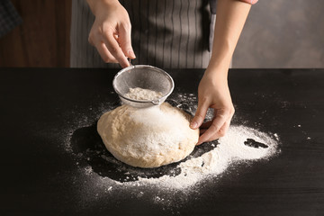 Young woman sifting flour over dough on table
