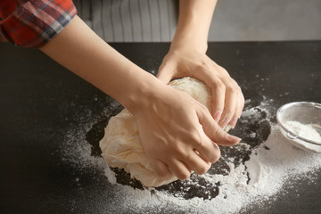 Woman kneading dough on kitchen table
