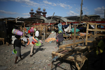 Vendors carry goods as they walk next to new stands at a market that was destroyed during a fire last week in Port-au-Prince