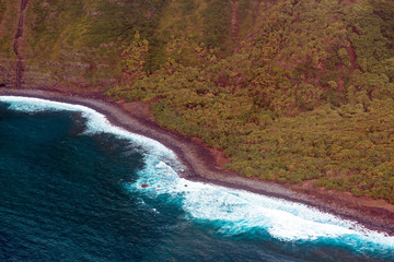 Aerial view of the curvy coastline, beach, and pounding surf on the island of Molokai, Hawaii, shot from a small, low-flying prop plane