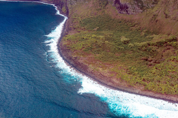 Aerial view of the curvy coastline, green shore, and pounding surf on the island of Molokai, Hawaii