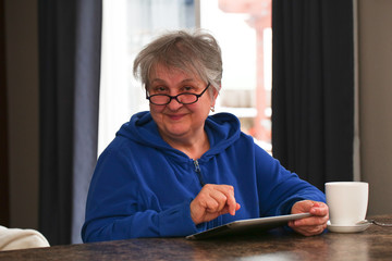 Beautiful, Mature, Elder, Grandmother, Woman with Grey Hair, in Eyeglasses is Using a Digital Tablet, Smiling, at home