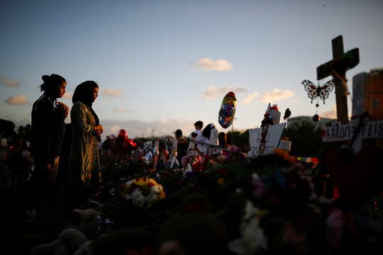 People grieve in front of crosses and Stars of David placed in front of the fence of the Marjory Stoneman Douglas High School to commemorate the victims of the mass shooting, in Parkland