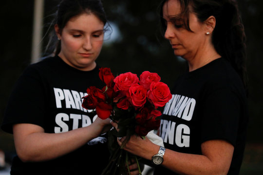 Heather Mesch and her daughter Alexa hold roses before placing them next to crosses and Stars of David placed in front of the fence of the Marjory Stoneman Douglas High School to commemorate the victims of the mass shooting, in Parkland