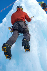 Alpinist man with ice tools axe climbing a large wall of ice. Outdoor portrait