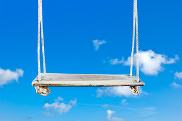 Wooden swing with blue sky background.