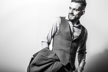 Handsome young elegant man in grey classic vest pose against studio background.