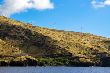 A wind farm rises above Honoapillani Highway 30 as it passes along Papawai Point on the northwest coast of Maui, shot from a boat on the open water