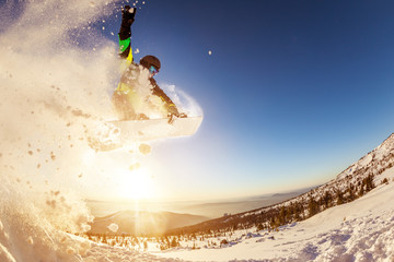 Snowboarder jumps against sunset sun