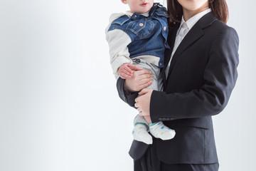 子供を抱くビジネスウーマン