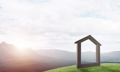 Conceptual image of concrete home sign on hill and natural landscape at background