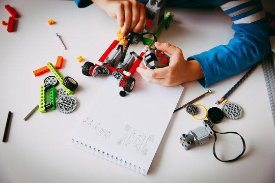 little boy building robot at robotic technology school lesson