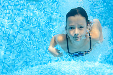 Child swims in swimming pool underwater, happy active girl dives and has fun under water, kid fitness and sport on family vacation on resort