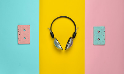 Wireless headphones and audio cassettes on a multicolored pastel paper background. Minimal creative art. Musical retro vibrations. Top view..