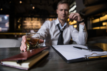 Closeup of an tired businessman sitting in restaurant and drinkin