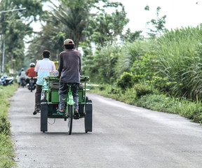 people pedal a pedicab, in the village, in the morning.