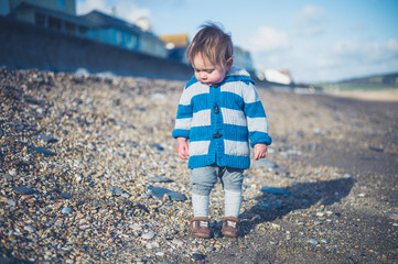 Cute little boy standing on the beach in winter