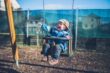 Happy little boy on swing in playground