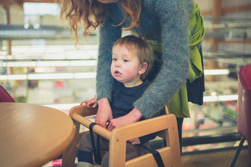 Young mother putting child in seat