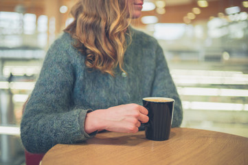 Young woman drinking coffee in airport