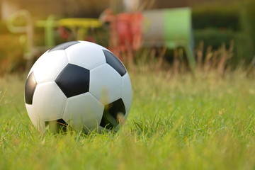 Football or soccer ball on green grass with morning sunlight and playground background, outdoor activities..