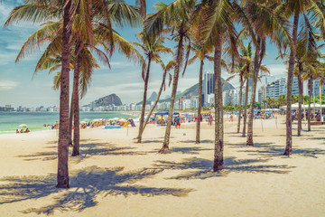 Sunny day with palm trees on Copacabana Beach. Summer time. Rio de Janeiro, Brazil