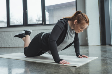 Overweight girl doing push ups in gym