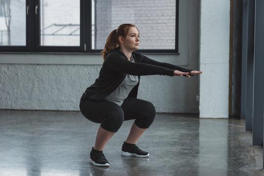 Curvy girl doing squat in gym