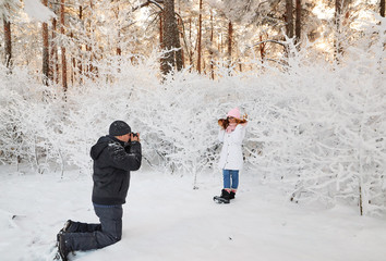 A photographer and a girl in a winter forest covered with snowy branches of trees. fairy beauty.