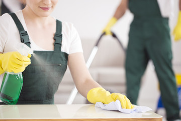 Cleaning lady spraying table