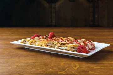 sweet gourmet rolled pancakes with raspberries and syrup