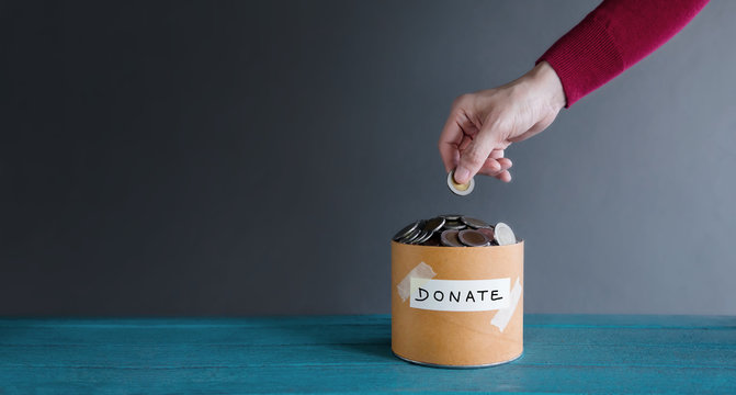 Donation Concept. Hand putting Money Coin into a Donate Box