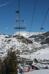 Chairlift at Italian ski area on snow covered Alps and pine trees during the winter, winter sports concept