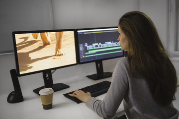Beautiful female video editor works with footage on her personal computer