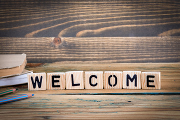 Welcome. Wooden letters on the office desk, informative and communication background.