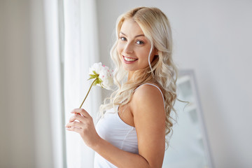 woman in underwear smelling flower at window