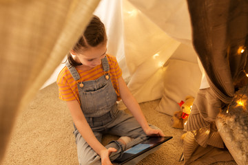 little girl with tablet pc in kids tent at home