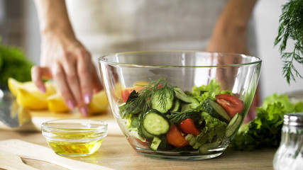 Lady holding lemon piece and olive oil for dressing, organic salad bowl on table