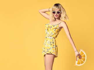 Glamour Short-haired girl in Fashionable Sunglasses Dancing. Young Hipster female Blond model in Stylish fashion Summer Outfit. Beautiful woman Having Fun dance in Studio on Yellow