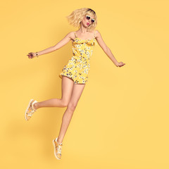 Short-haired Happy girl Jumping in Fashionable Sunglasses. Young Playful female Blond model in Stylish fashion Summer Outfit on Yellow background. Beautiful woman Fooling Around in Studio