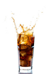 Ice splashing on a glass of a Cola drink against a white background