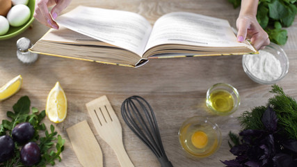 Woman hands holding cooking book table, girl choosing recipe for family dinner