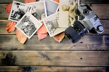 Closeup of vintage photo and camera on antique wooden table and leaves background