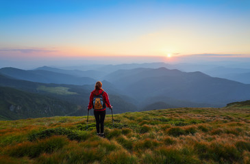 Redheaded girl athlete with a backpack and sticks stands on the green hillocks and looks at high mountain landscapes and fascinating sunset. Location place Carpathian national park, Ukraine, Europe.