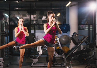 Two beautiful sporty active young girl doing side kicks for gluteus and legs muscles in the gym.