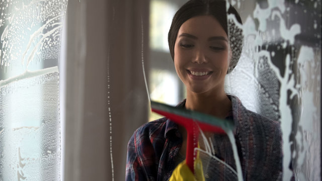 Young happy woman wiping glass surface after spray, cleaning service quality